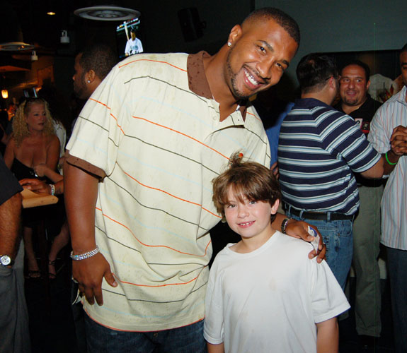 Miami Dolphins quarterback Daunte Culpepper poses with a young fan at the grand opening celebration of Rivals at the Westin Diplomat in Hollywood Beach, Fla.