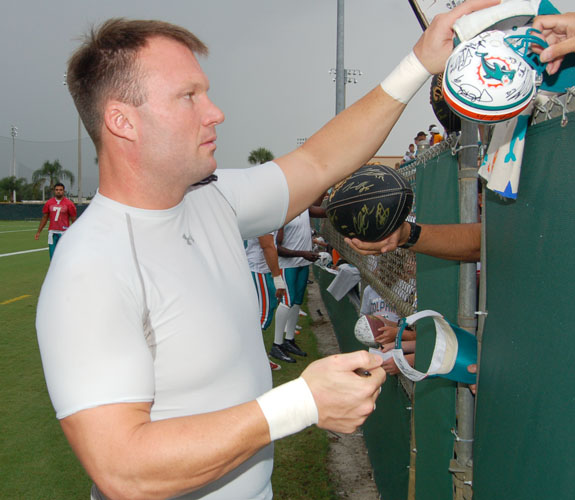 Miami Dolphins linebacker Zach Thomas signs autographs for fans after practice at the team's training facility in Davie, Fla.